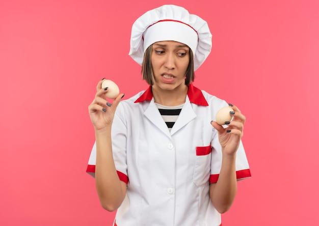 ピンクの背景に分離された卵を保持し、見てシェフの制服を着た不機嫌な若い女性料理人