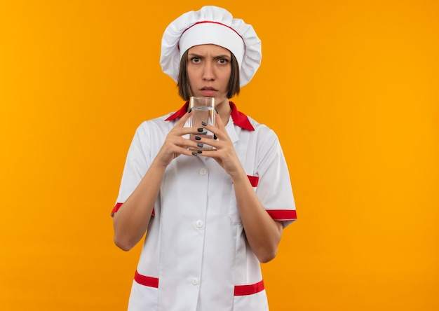 コピースペースでオレンジ色の背景に分離されたカメラを見て水のガラスを保持しているシェフの制服を着た不機嫌な若い女性料理人