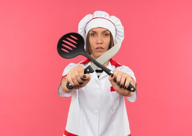 ヘラとナイフを保持し、コピースペースでピンクの背景に分離されたカメラで彼らと一緒に身振りで示すシェフの制服を着た不機嫌な若い女性料理人