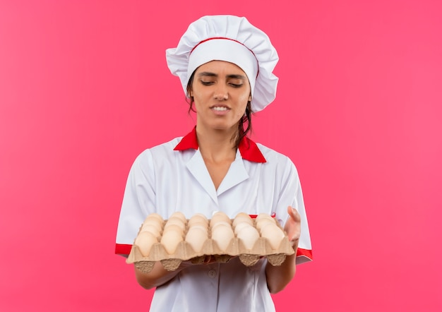 コピースペースで卵のバッチを保持し、見てシェフの制服を着て不機嫌な若い女性料理人
