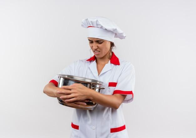 コピースペースのある鍋を持って見ているシェフの制服を着た不機嫌な若い女性料理人