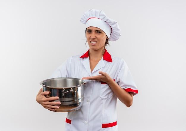 不機嫌そうな若い女性料理人がシェフの制服を持って、コピースペースのある孤立した白い壁に鍋を手で指しています