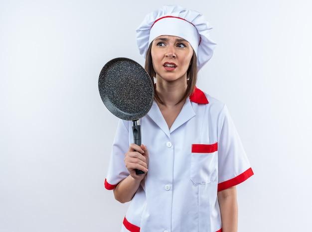 白い背景で隔離のフライパンを保持しているシェフの制服を着て不機嫌な若い女性料理人