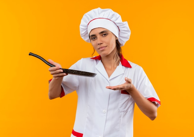 Unpleased young female cook wearing chef uniform holding and points with hand to frying pan  with copy space