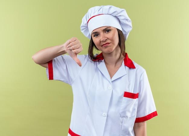 オリーブグリーンの壁に隔離された親指を下に示すシェフの制服を着て不機嫌な若い女性料理人