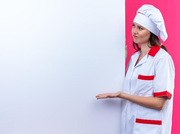 シェフの制服を着た不機嫌な若い女性料理人が白い壁の近くに立って、コピースペースのあるピンクの壁に隔離された手で壁を指しています