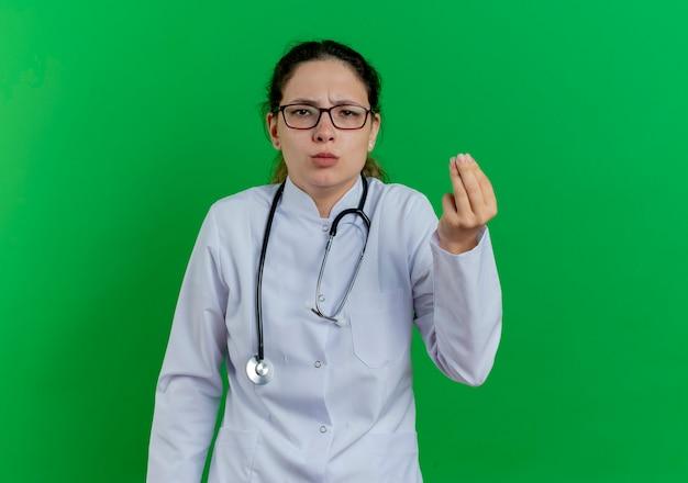 コピースペースで緑の壁に隔離されたお金のジェスチャーをしている医療ローブと聴診器と眼鏡を身に着けている不機嫌な若い女性医師