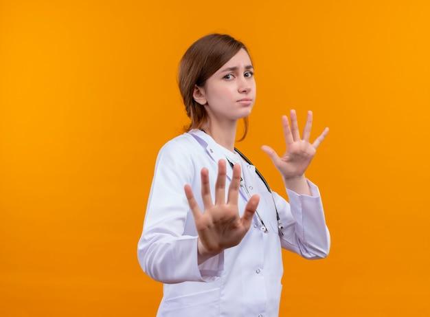 コピースペースのある孤立したオレンジ色の壁にジェスチャーをしない医療ローブと聴診器を身に着けている不機嫌な若い女性医師