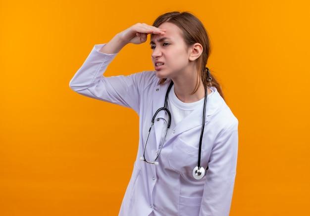 医療ローブと聴診器を身に着けている不機嫌な若い女性医師が額の近くに手を置き、孤立したオレンジ色の壁で距離を見て
