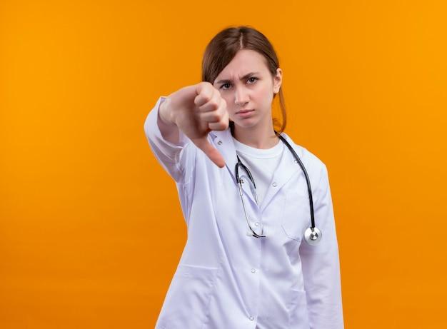 コピースペースと孤立したオレンジ色の壁に親指を下に示す医療ローブと聴診器を身に着けている不機嫌な若い女性医師