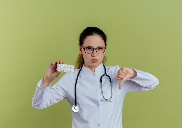 Недовольная молодая женщина-врач в медицинском халате и стетоскоп в очках, держа таблетки, показывая большой палец вниз, изолированную на оливково-зеленой стене