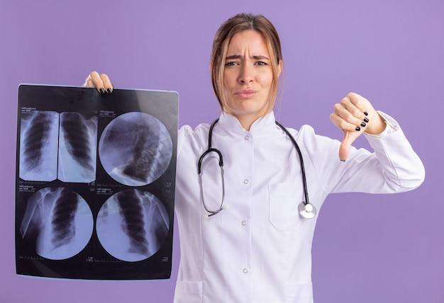 Giovane dottoressa scontenta che indossa una tunica medica con uno stetoscopio che tiene i raggi x che mostra il pollice verso il basso isolato sulla parete viola
