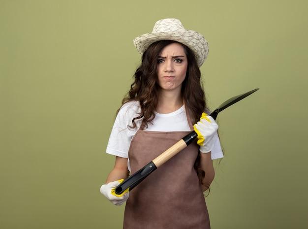 園芸帽子と手袋を身に着けている制服を着た不機嫌な若い女性の庭師は、オリーブグリーンの壁に隔離されたスペードを保持します