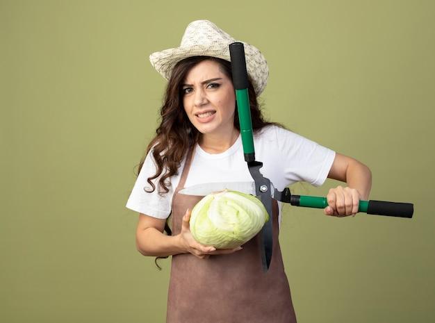 Недовольная молодая женщина-садовник в униформе в садовой шляпе держит садовые ножницы и капусту, изолированные на оливково-зеленой стене