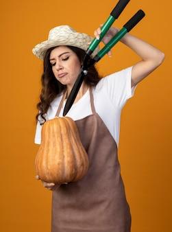 Недовольная молодая женщина-садовник в униформе в садовой шляпе держит садовые ножницы над тыквой, изолированной на оранжевой стене с копией пространства