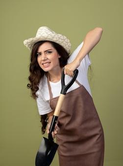 ガーデニング帽子をかぶって制服を着た不機嫌な若い女性の庭師は、オリーブグリーンの壁に隔離されたスペードを保持