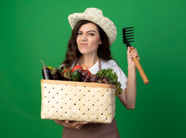 ガーデニング帽子を身に着けている制服を着た不機嫌な若い女性の庭師は、緑の壁に隔離された野菜のバスケットと熊手を保持します