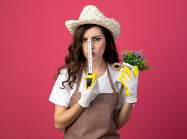 Il giovane giardiniere femminile dispiaciuto in uniforme che indossa il cappello e i guanti di giardinaggio tiene il vaso di fiori e la misura di nastro isolata sulla parete rosa con lo spazio della copia