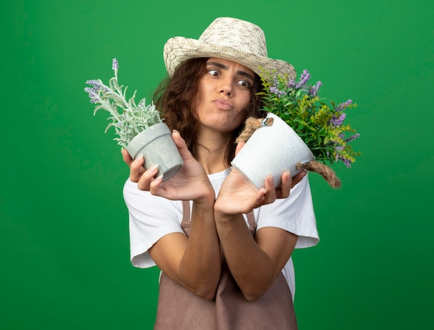 Giovane giardiniere femminile dispiaciuto in uniforme che indossa cappello da giardinaggio tenendo e guardando i fiori in vasi da fiori