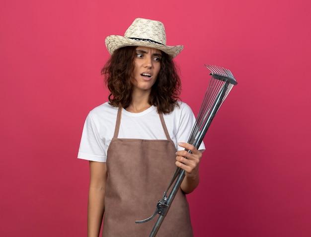Giovane giardiniere femminile dispiaciuto in uniforme che porta il cappello di giardinaggio che tiene e che esamina il rastrello del foglio