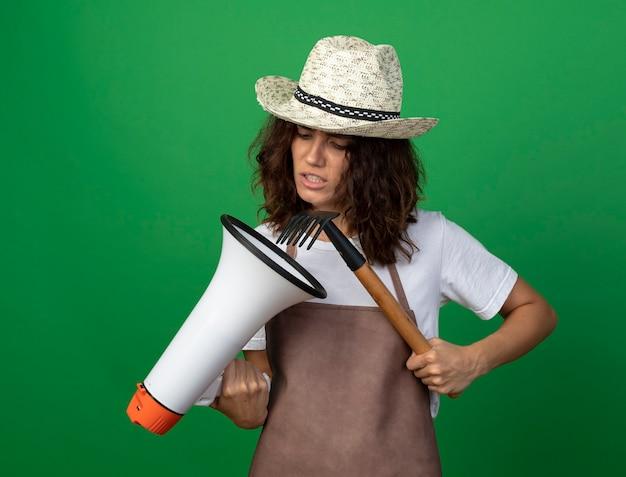 Giardiniere femminile giovane dispiaciuto in cappello da giardinaggio d'uso uniforme che tiene e che guarda altoparlante con il rastrello