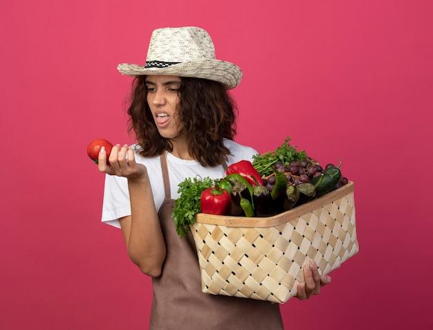 Giovane giardiniere femminile dispiaciuto in cappello da giardinaggio da portare uniforme che tiene il cestino della verdura e che esamina il pomodoro in sua mano isolata sul colore rosa