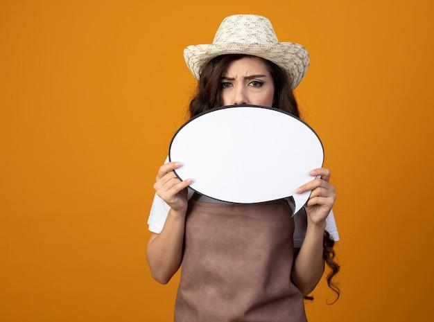 Il giovane giardiniere femminile dispiaciuto in cappello da giardinaggio da portare uniforme tiene il fumetto isolato sulla parete arancione