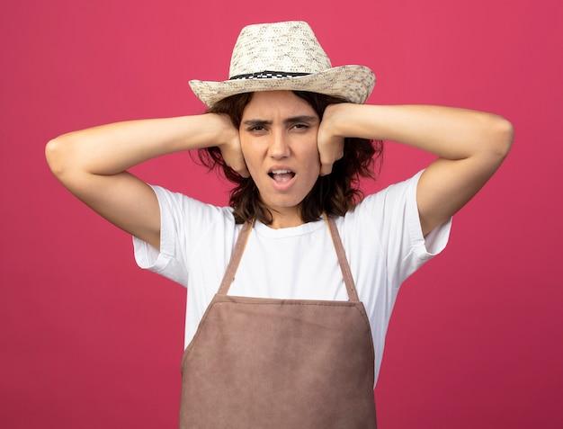 Giardiniere femminile giovane dispiaciuto in cappello da giardinaggio d'uso uniforme che mette le mani sulle orecchie