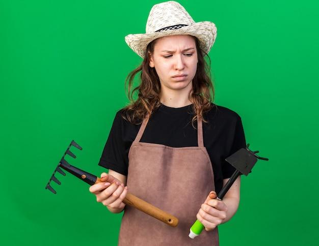 ガーデニングの帽子をかぶって、くわの熊手で熊手を見て不機嫌な若い女性の庭師