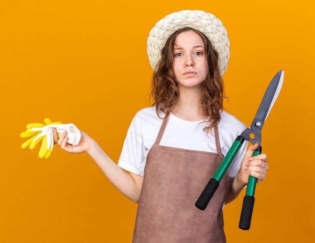 オレンジ色の壁に隔離された手袋で剪定ばさみを保持しているガーデニング帽子をかぶっている不機嫌な若い女性の庭師
