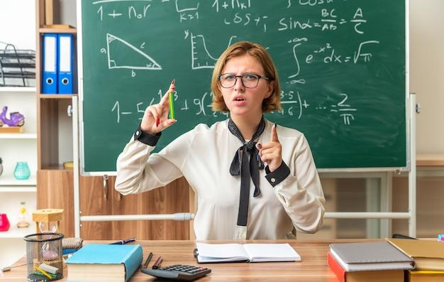 불쾌한 젊은 여교사는 교실에서 몸짓을 보여주는 연필을 들고 학용품을 들고 탁자에 앉아 있다