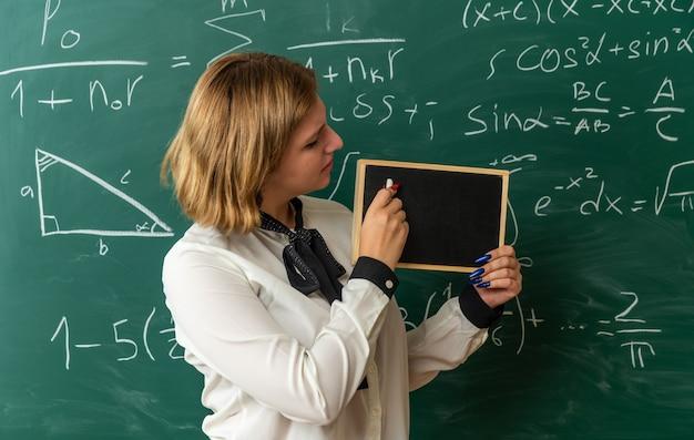Scontenta giovane insegnante femminile in piedi davanti alla lavagna tenendo e guardando la mini lavagna con incagliato per la lavagna in classe