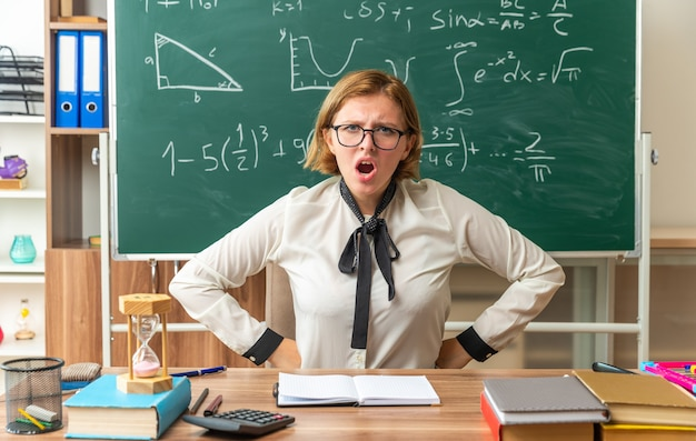 眼鏡をかけている不機嫌な若い女性教師は、教室で腰に手を置く学用品とテーブルに座っています