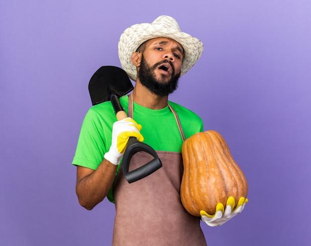 Ragazzo afroamericano del giovane giardiniere scontento che indossa cappello e guanti di giardinaggio che tengono zucca che mette vanga sulla spalla isolata sulla parete blu
