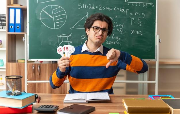 안경을 쓰고 교실에서 학용품을 들고 책상에 앉아 있는 불쾌한 젊은 기하학 교사는 숫자 팬과 엄지손가락을 아래로 보여주는 앞을 바라보고 있습니다