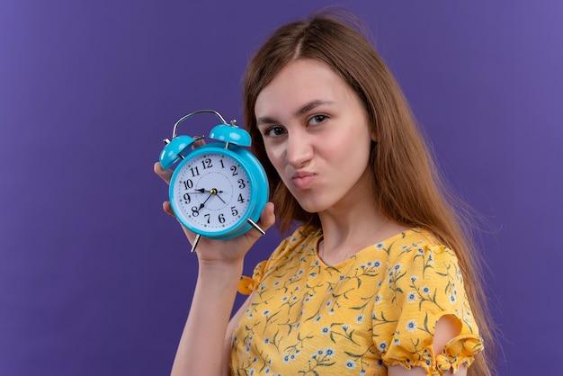 Ragazza giovane dispiaciuta che tiene sveglia sulla parete viola isolata