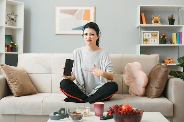 Недовольная молодая девушка держит и указывает на телефон, сидя на диване за журнальным столиком в гостиной