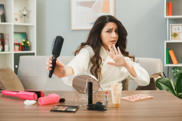 Недовольная молодая девушка, держащая гребень, сидит за столом с инструментами для макияжа в гостиной