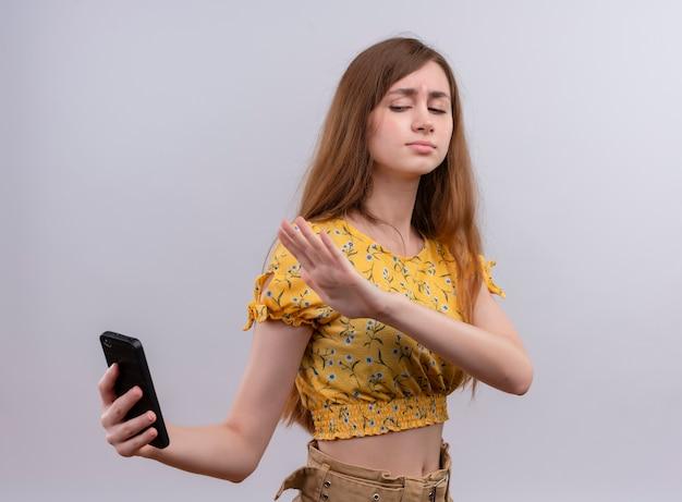 Ragazza giovane dispiaciuta che tiene il telefono cellulare e che indica con la mano sulla parete bianca isolata