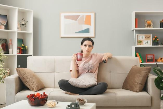 Ragazza scontenta che tiene il telecomando della tv con una tazza di tè seduta sul divano dietro il tavolino da caffè nel soggiorno