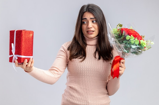Unpleased young girl on valentines day holding bouquet looking at gift box in her hand isolated on white background
