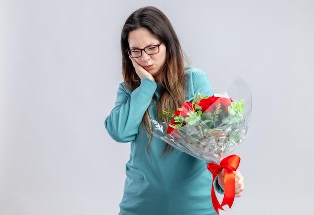 Ragazza scontenta il giorno di san valentino che tiene e guarda il bouquet mettendo la mano sulla guancia isolata su sfondo bianco