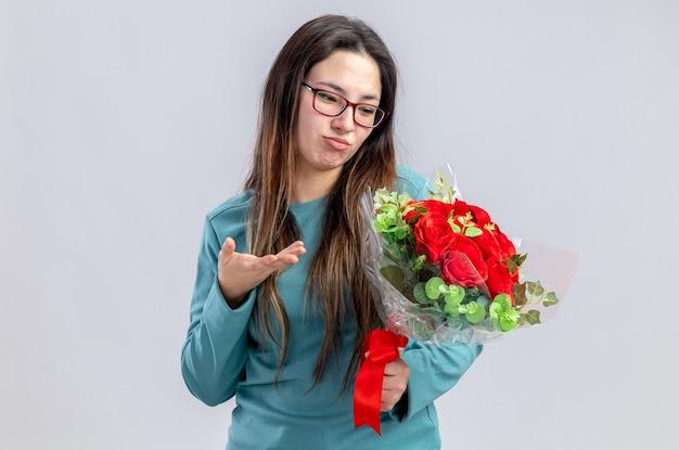 Ragazza scontenta il giorno di san valentino che tiene e punta con la mano al bouquet isolato su sfondo bianco
