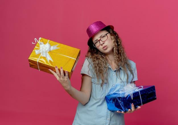 ピンクの壁に隔離されたギフトボックスを保持している眼鏡とピンクの帽子を身に着けている不機嫌な少女
