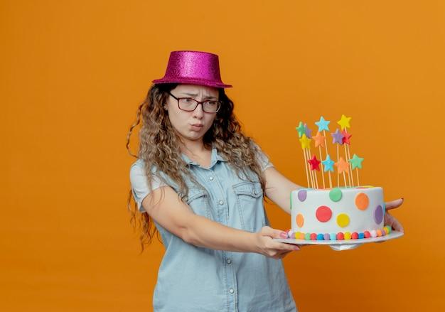 Недовольная молодая девушка в очках и розовой шляпе держит рядом торт ко дню рождения