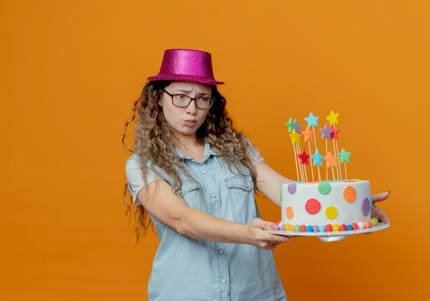 Unpleased young girl wearing glasses and pink hat holding out birthday cake at side
