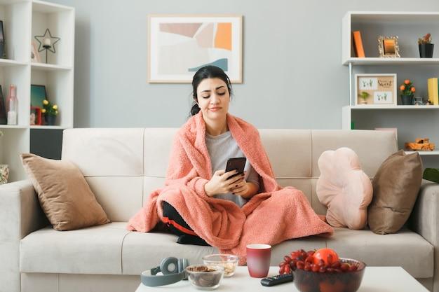 Недовольная молодая девушка, завернутая в плед, держит и смотрит в телефон, сидя на диване за журнальным столиком в гостиной
