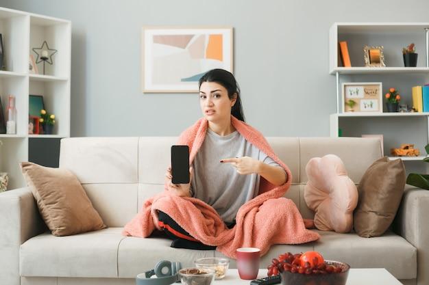 Недовольная молодая девушка, завернутая в плед, и указывает на телефон, сидя на диване за журнальным столиком в гостиной