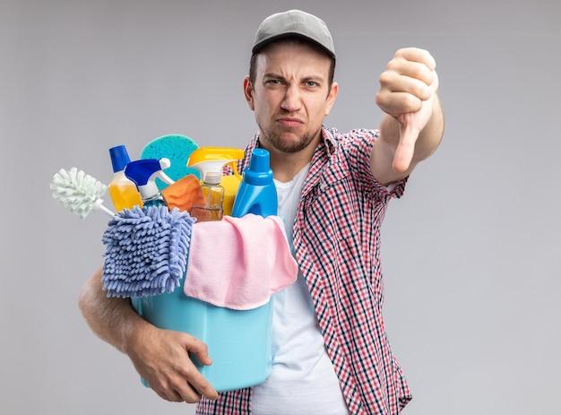白い壁に隔離された親指を示すクリーニングツールとバケツを保持しているキャップを身に着けている不機嫌な若い男クリーナー