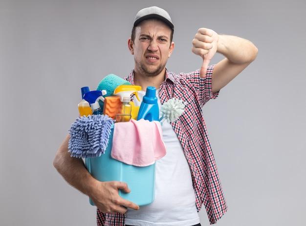 흰색 벽에 격리된 엄지손가락을 보여주는 청소 도구가 있는 양동이를 들고 모자를 쓴 불쾌한 젊은 남자 청소기
